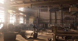 De kraanbewegingen van de fabrieksstraal bovenop een grote lassenworkshop De arbeiders lassen metaalstructuren bij installatie en stock footage