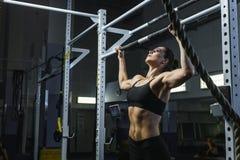 De krachtige aantrekkelijke trainer van vrouwencrossfit trekt UPS tijdens training stock foto