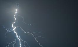 De krachtige bliksem slaat de grond tijdens onweer stock foto