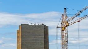De kranen van de Timelapsebouw, die tegen bewogen wolk bouwen bij blauwe hemel stock video