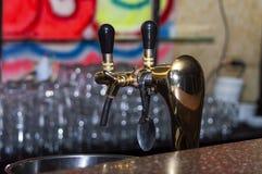 De kranen van het koperbier in een donkere bar stock foto's