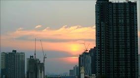 De kranen werken aan de bouwwerf met de het plaatsen zon en mooie hemel op achtergrond stock videobeelden