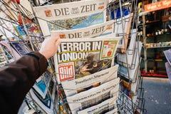 De krant van de Matrijzenbild van mensenaankopen van perskiosk na Londen royalty-vrije stock fotografie