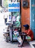 De krant van de mensenlezing buiten een winkel royalty-vrije stock afbeeldingen