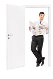 De krant van de mensenlezing en het leunen van een deur Stock Fotografie