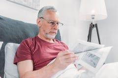 De krant van de mensenlezing terwijl thuis het liggen in bed Royalty-vrije Stock Afbeeldingen