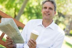 De krant van de zakenmanholding en koffiekop in park Royalty-vrije Stock Foto