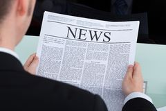 De krant van de zakenmanlezing bij bureau Stock Foto's