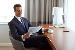 De krant van de zakenmanlezing en het drinken koffie Stock Foto's
