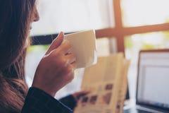 De krant van de vrouwenlezing en het drinken koffie terwijl het gebruiken van laptop in de ochtend in bureau royalty-vrije stock foto