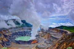 De krater van de Poá s vulkaan met de wolken van de zwaveldamp stock fotografie