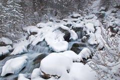 De kreek van de winter tijdens sneeuwval Stock Afbeeldingen