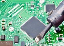 De kringsraad van de computer met ijzer het solderen Stock Afbeelding