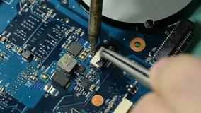 De kringsraad van de reparatiecomputer: solderende schakelaar op laptop motherboard stock video