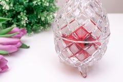 De kristalkom in de vorm van paaseieren met de lente bloeit tulipsn en een installatie op een witte lijst stock foto