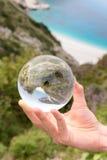 De kristallen bol van de handholding dichtbij overzees en berg royalty-vrije stock fotografie