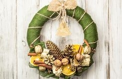 De kroon van komstkerstmis met decoratie die op houten deur hangen Royalty-vrije Stock Foto