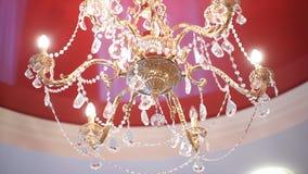 De kroonluchter van het luxekristal op het rode plafond Mooie kristalkroonluchter in omringend licht Royalty-vrije Stock Foto