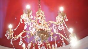 De kroonluchter van het luxekristal op het rode plafond Mooie kristalkroonluchter in omringend licht Stock Fotografie