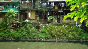 De krottenwijken huisvest dichtbij verontreinigde rivieroever stock footage