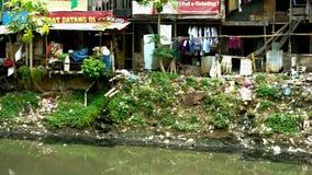 De krottenwijken huisvest dichtbij vuile rivier stock video