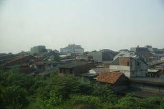 De krottenwijkengebied van Djakarta van een bewegende trein wordt gezien die stock foto