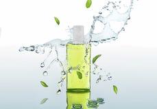 De kruiden bevochtigende shampoo bevindt zich op de waterachtergrond met plonsen en muntbladeren Stock Afbeeldingen