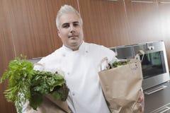 De Kruidenierswinkels van chef-kokwith bags of in Commerciële Keuken stock afbeeldingen