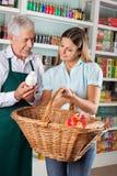 De Kruidenierswinkels van verkopersassisting customer buying stock foto