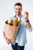 De kruidenierswinkelzak en appel die van de mensenholding bij camera glimlachen Royalty-vrije Stock Afbeelding