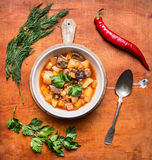 De kruidige soep met lam en de groenten, aardappels in witte platen lepelen groene kruidige Spaanse peper Stock Afbeeldingen