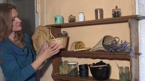 De kruidkundigevrouw bereidt droge kruiden in rieten manden voor de wintertijd voor 4K stock videobeelden