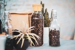 De kruik glas met een Wijn kurkt deksel met Koffiebonen op oude houten Teller stock foto's