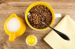 De kruik melk, zout, kookte boekweit, lepel in gele kom, servet op lijst Hoogste mening stock foto's