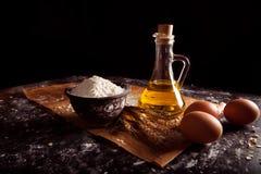 De kruik met olie, ongezuurde broodjes, ei, vormt een bloem tot een kom Stock Foto