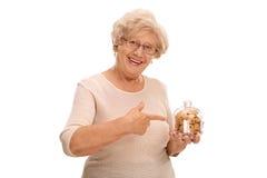 De kruik van de bejaardeholding koekjes en het richten royalty-vrije stock foto