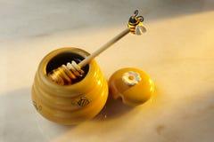De kruik van de honing en honingsdripper stock foto's