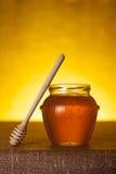 De kruik van de honing met dipper op lijst stock afbeeldingen