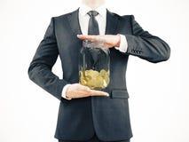 De kruik van de zakenmanholding met muntstukken Stock Fotografie