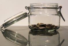 De kruik van het besparingsgeld met kleine stapel van muntstukken stock foto's