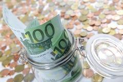 De kruik van het glas met Euro rekeningen en muntstukken Stock Afbeeldingen