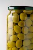 De kruik van het glas van bewaarde olijven Stock Foto's