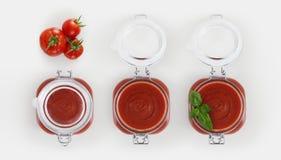 De kruik van het tomatensausglas met tomaten en basilicum op wit royalty-vrije stock foto