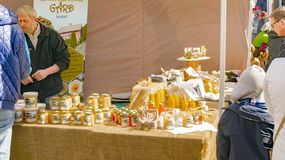 De kruiken met honingraatproducten en de bij zetten kaarsen op gelei Stock Foto