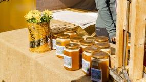 De kruiken met honingraatproducten en de bij zetten kaarsen op gelei Stock Afbeeldingen