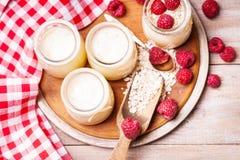 De kruiken met yoghurt, frambozen, houten lepel, lepel en haver schilfert af royalty-vrije stock foto