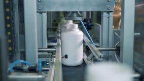 De kruiken plastiek worden door de dringende machine worden gevuld die stock video
