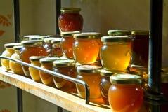 De kruiken van de honing op een plank Stock Foto's