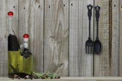 De kruiken van het oliekruid met gietijzerlepel en vork tegen houten achtergrond Stock Foto