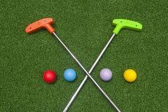 De kruising van Mini Golf Putters met Vier Ballen stock fotografie